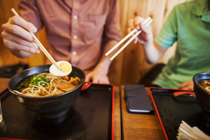 Two people, a Japanese man showing a Western man how to use chopsticks in a noodle shop.の写真素材 [FYI02260304]
