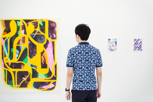 Rear view of man with short black hair wearing blue shirt standing in art gallery, looking at abstraの写真素材 [FYI02260307]