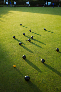 Lawn bowls balls positioned on a smooth playing surface, a bowls green. One small yellow jack ball.の写真素材 [FYI02260315]
