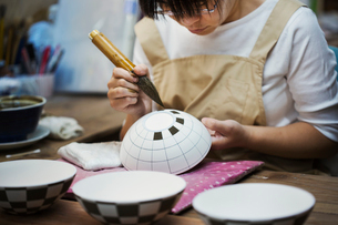 Close up of woman working in a Japanese porcelain workshop, painting geometric pattern onto white boの写真素材 [FYI02260322]