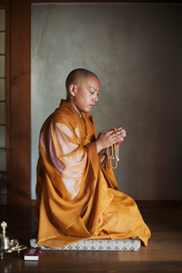 Side view of Buddhist monk with shaved head wearing golden robe kneeling indoors in a temple, holdinの写真素材 [FYI02260324]