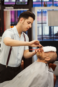 A customer sitting in the barber's chair, with a hot towel on his face, and a barber trimming his beの写真素材 [FYI02260336]