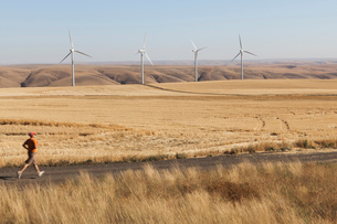 Man jogging on rural road, farmland and wind turbines in distance, Washingtonの写真素材 [FYI02260337]