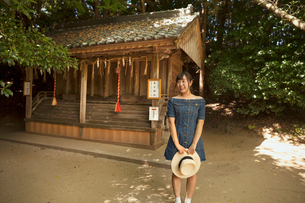 Young woman wearing blue dress and holding hat standing at Shinto Sakurai Shrine, Fukuoka, Japan.の写真素材 [FYI02260344]