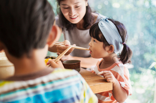 Young girl with black pigtails and blue hairband, boy and woman sitting at a table.の写真素材 [FYI02260361]