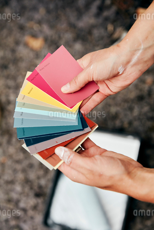A person holding a paint colour chart, and a paint tray and roller in the background.の写真素材 [FYI02260366]
