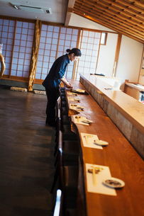 Waitress standing at a counter in a Japanese sushi restaurant, preparing place settings.の写真素材 [FYI02260372]