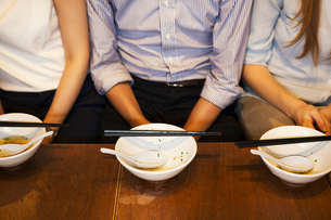 High angle close up of three people sitting sidy by side at a table in a restaurant, empty bowls witの写真素材 [FYI02260390]