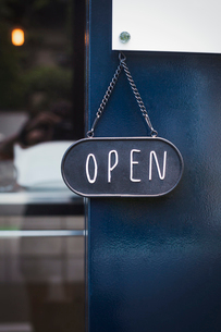 Close up of open sign on glass door to a bakery.の写真素材 [FYI02260395]