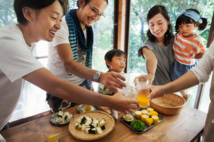 Two men, woman holding young girl and boy gathered around a table with food, holding drinking glasseの写真素材 [FYI02260402]