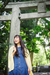 Smiling young woman wearing blue dress and yellow shirt at Shinto Sakurai Shrine, Fukuoka, Japan.の写真素材 [FYI02260410]