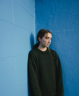 Portrait of teenage girl with brown hair in ponytail wearing black knitted jumper, leaning against bの写真素材 [FYI02260414]