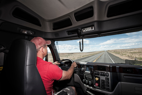 Interior cab view of a Caucasian man driving his  commercial truck.の写真素材 [FYI02260430]