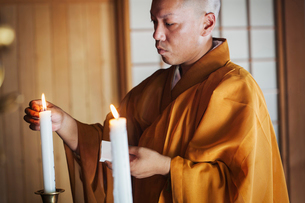 Side view of Buddhist monk with shaved head wearing golden robe kneeling indoors in a temple, lightiの写真素材 [FYI02260433]