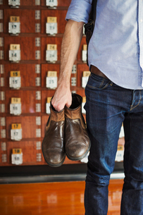 A man holding boots in his hand, shoe lockers in rows behind him.の写真素材 [FYI02260441]