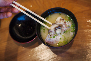 High angle close up of a bowl with soup and piece of fish in Japanese sushi restaurant.の写真素材 [FYI02260463]