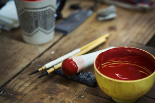 Close up materials in a Japanese porcelain workshop, bowl with red paint, pestle and paintbrushes.の写真素材 [FYI02260470]