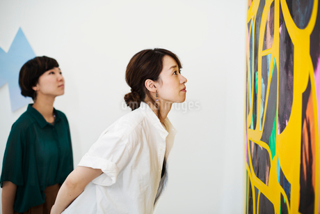Two women standing in an art gallery, looking at an abstract modern painting.の写真素材 [FYI02260478]