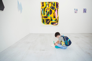 Boy with short black hair wearing backpack sitting on floor in art gallery with pen and paper, lookiの写真素材 [FYI02260483]