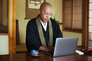 Buddhist monk with shaved head wearing black robe sitting indoors at a table, using laptop computer.の写真素材 [FYI02260494]