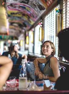 Smiling woman sitting in a booth in a diner looking up and talking to friends.の写真素材 [FYI02260505]