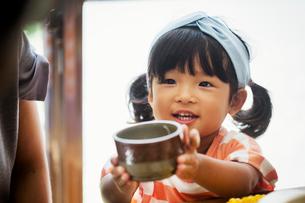 Close up of young girl with black pigtails and blue hairband holding a ceramic bowl.の写真素材 [FYI02260512]