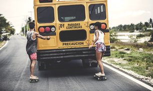 Two young people skateboarding while holding on to a moving school bus.の写真素材 [FYI02260513]