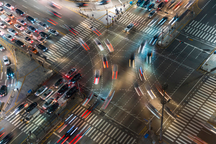 High angle view of busy urban street junction with pedestrian crossing at night, light trails of carの写真素材 [FYI02260532]