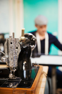 A retro style traditional sewing machine with chased metalwork, and a tailor working in the backgrouの写真素材 [FYI02260545]