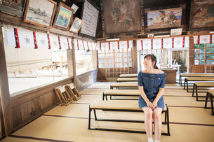 Young woman wearing blue dress sitting on bench  at Shinto Sakurai Shrine, Fukuoka, Japan.の写真素材 [FYI02260547]