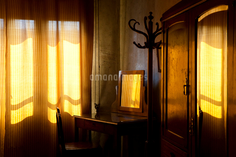 Room interior with vintage wooden dressing table with mirror, hat stand and wardrobe, yellow light fの写真素材 [FYI02260552]