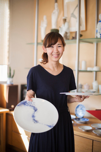 Smiling woman standing in a Japanese porcelain shop, holding two white plates with blue decoration.の写真素材 [FYI02260560]