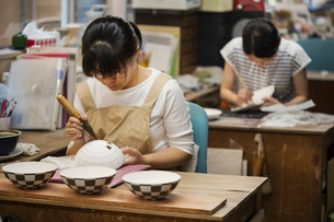 Woman working in a Japanese porcelain workshop, painting geometric pattern onto white bowls with paiの写真素材 [FYI02260562]