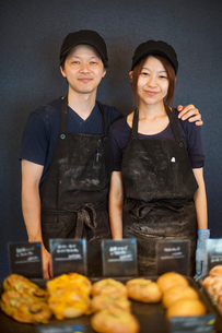 Smiling man and woman wearing baseball cap and apron standing in a bakery, trays with freshly bakedの写真素材 [FYI02260569]