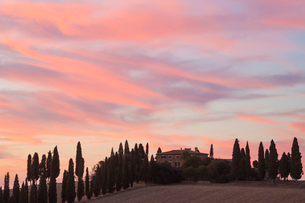 Sunset across a cloudy Italian landscape with cypress trees and farmhouse.の写真素材 [FYI02260574]