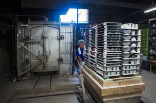 Interior view of Japanese porcelain workshop, man preparing large stack of porcelain objects for kilの写真素材 [FYI02260583]