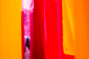 Close up of freshly dyed bright yellow and pink fabric hanging up to dry.の写真素材 [FYI02260591]