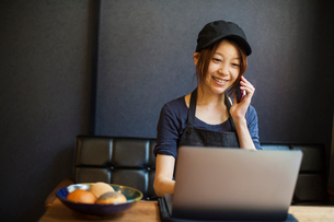 Woman working in a bakery, wearing baseball cap, sitting at table in front of laptop, using mobile pの写真素材 [FYI02260602]