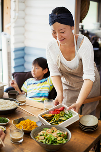 Smiling woman wearing apron placing bowls of salad and vegetables on a table, boy sitting in backgroの写真素材 [FYI02260618]
