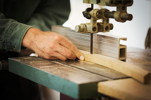 A craftsman using a machine drill on a piece of smooth planed shaped wood.の写真素材 [FYI02260624]