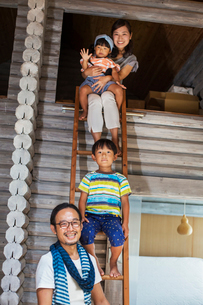 Family, man, woman, boy and young girl sitting on a ladder, smiling at camera.の写真素材 [FYI02260634]