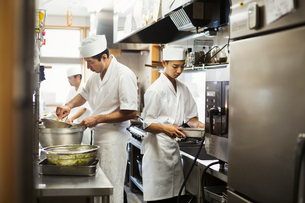 Two chefs working in the kitchen of a Japanese sushi restaurant.の写真素材 [FYI02260643]