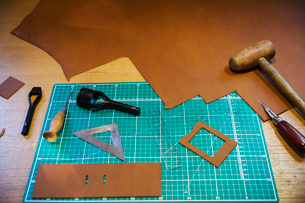 Workbench and cutting mat with a large smooth piece of brown leather, and tools for measuring cuttinの写真素材 [FYI02260650]