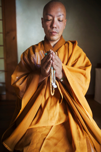 Buddhist monk with shaved head wearing golden robe kneeling indoors in a temple, holding mala, prayiの写真素材 [FYI02260661]