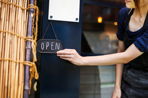 Close up of woman turning open sign on glass door to a bakery.の写真素材 [FYI02260662]
