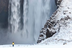 Winter landscape with rear view of person standing next to a tall waterfall.の写真素材 [FYI02260685]