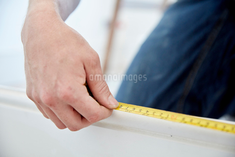 A man using a steel measuring tape.の写真素材 [FYI02260691]