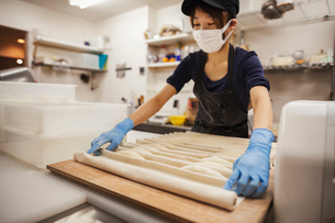Woman working in a bakery, wearing protective gloves and mask, placing dough on large wooden board.の写真素材 [FYI02260699]