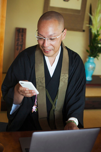 Buddhist monk with shaved head wearing black robe sitting indoors at a table in front of laptop compの写真素材 [FYI02260706]