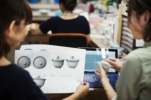 Two women sitting in a workshop at laptop, holding drawing of  Japanese porcelain cups and lids.の写真素材 [FYI02260708]